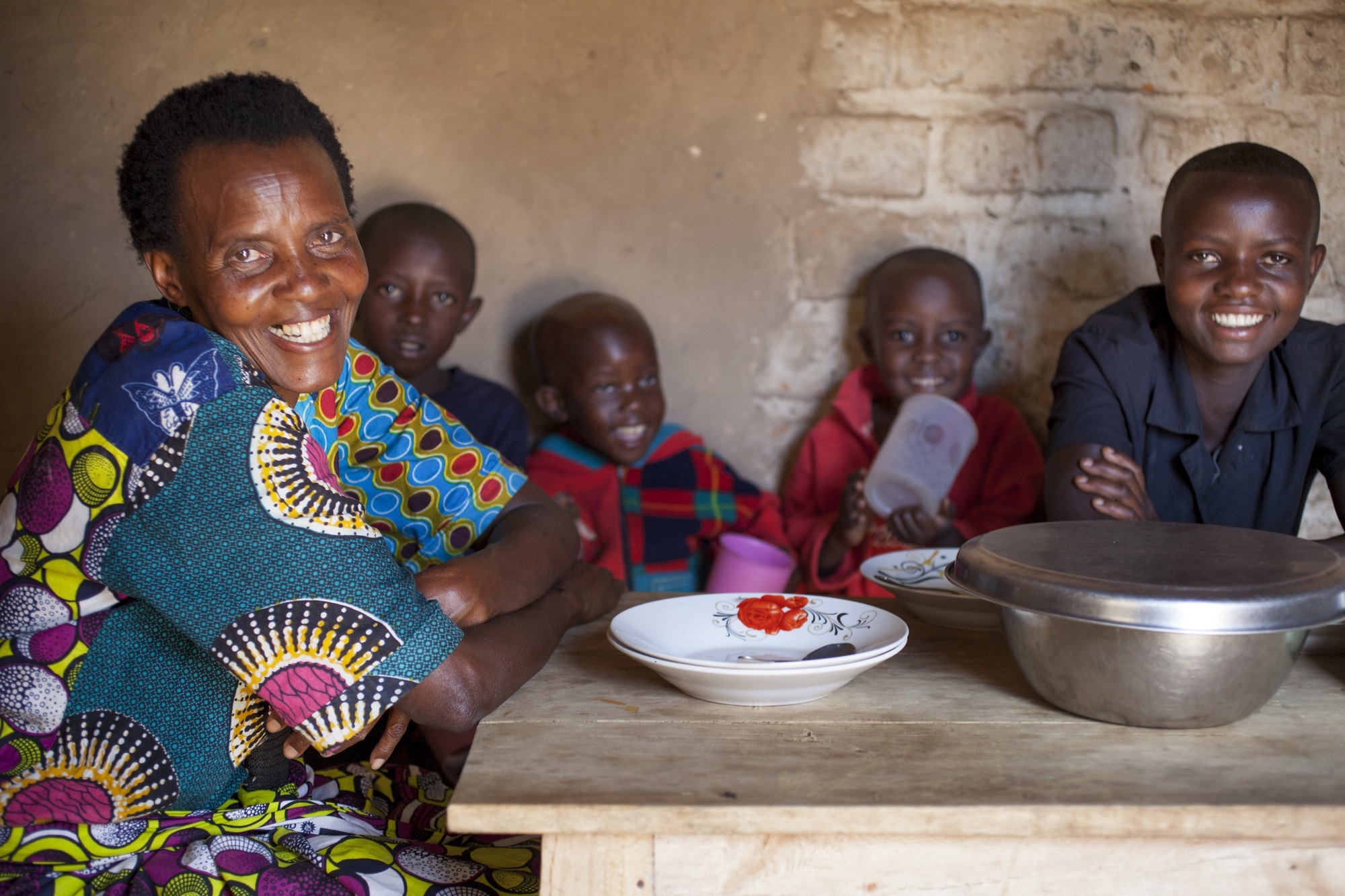 Violette Bukeyeneza sits at her new kitchen table and chairs with her children. Photo: Abbie Trayler-Smith