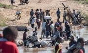 People wade across a river in flood near Nhamatanda, Mozambique. Cyclone Idai has disrupted infrastructure across the country, impacting livelihoods and hampering aid efforts. Photo: Tommy Trenchard / Concern Worldwide