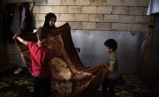 Syrian refugee *Dibeh, folds blankets with her sons which have been donated by Concern. Photo: Mary Turner