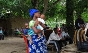 Kumba Kamara, mother of two, attends a Covid-19 sensitaization meeting under mango trees at Bassia Village organised by Concern. Photo: Mohamed Saidu Bah