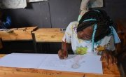 Sheila from Kenya in class drawing what she wants to be when she grows up.
