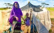 Sori with her son Abudho in Kalacha, Marsabit, standing outside their kitchen garden full surrounded by desert. This season the harvest will include butternut squash, watermelon and spinach. Photo: Jennifer Nolan / Concern Worldwide