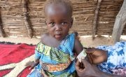 Rafaida, one and a half years old, having her MUAC measurement taken by her mother Khamissa in Doroti, Chad, 2018. Khamissa is a Concern-trained Community Health Volunteer. Photo: Lucy Bloxham / Concern Worldwide.