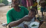 Mama Lumiere Nadine Doko demonstrates to her neighbours how to prepare a nutritious meal for their young children, by cooking a dish consisting of onions, squash leaves, peanut paste and oil. Photo: Darren Vaughan
