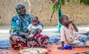 Nayla* prepares a meal of maize while her two sons Murad* and Jasim* wait. Photo: Gavin Douglas