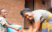 Ethel Nkhoma washes her hands above a bucket of water while her son Chisomo sits beside her.