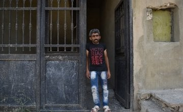 Syrian refugee *Jomaa is pictured in the doorway of the home he shares with his large family and their cousins after being moved by Concern as they were in danger. Photo: Mary Turner