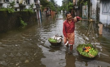 An Indian vegetable vendor carries his wares through floodwaters in Siliguri, West Bengal. Photo: AFP/Diptendu Dutta, 2016