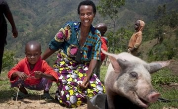 Violette and her son Lievain with the pig she has bought from the profits of her business at her home in Burundi. Photo: Abbie Trayler-Smith