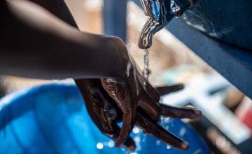 Trevor (4) washes his hands. Ambeza Idd, (35) (blue vest) mans the hand washing station. Kibera Slum, Nairobi, Kenya Photo: Ed Ram / Concern Worldwide