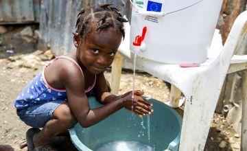 Cherica washes her hands in Cite Soleil slum, a district of Port-au-Prince, Haiti.