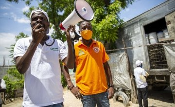 Staff talk to residents during distribution of hygiene kits in Port-au-Prince, Haiti. Photo: Dieu Nalio Chery