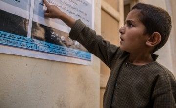 In Northern Afghanistan, Concern is raising awareness of the symptoms and preventative measures people can take in relation to Covid-19. Ghofran* (7) reads the sign. Photo: Stefanie Glinski