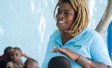 Jasmine listens as Woodson Marcelin tells a story during Children's Parliament activities in Cité Soleil, Port au Prince. Photo: Kieran McConville/ Concern Worldwide