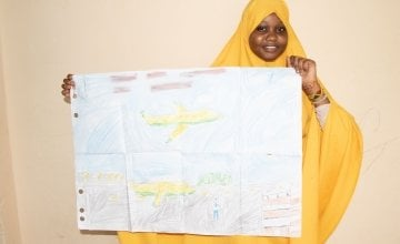 Fatuma from Somalia pictured with her artwork of what she wants to be when she grows up.