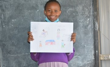 Glory from Kenya pictured with her drawing of what she wants to be when she grows up.