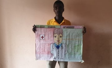 Mubarak pictured with his drawing of what he wants to be when he grows up, Somalia.