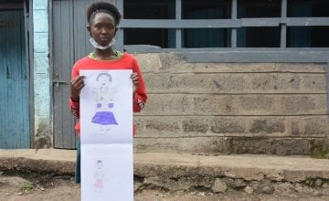 Jane from Kenya pictured holding her drawing of what she wants to be when she grows up.