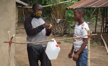 Alusine Baba Sesay (Left) a concern worldwide staff training a teen on construction of a local hand washing facility (TippyTap) after distributing soap and a water containers to households in the Tonkolili District, Sierra Leone. Photo: Mohamed Saidu Bah / Concern Worldwide.