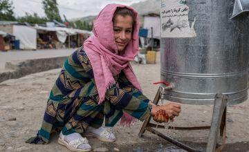 Kobra* washes their hands at the newly installed hand-washing station, Afghanistan. Photo: Stefanie Glinski