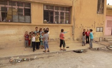 Children playing in their new home which is an abandoned school in Syria. Photographer: Arjan Ottens