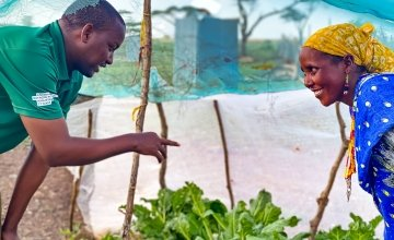 A Concern livelihood officer gives advice to gardener Roge on ways to keep her kale free of disease