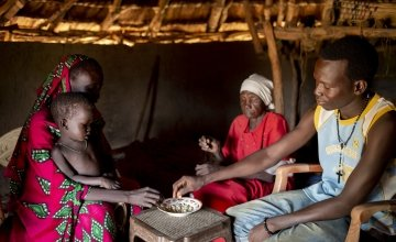 Nyarok* (25) with her daughter Axlam* (2 and a half) pictured in their home with her husband Makur* (24) and his grandmother Kazima* (60). They built and live in small tukel in a rural area of Aweil, South Sudan. Photo: Abbie Trayler-Smith / Concern Worldwide