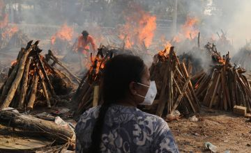 A family member looks on as several funeral pyres of patients who died of Covid-19 burn during the mass cremation at Ghazipur cremation ground in New Delhi, India. Photo: Naveen Sharma/SOPA Images/LightRocket via Getty Images