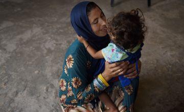 Syrian refugee *Nofah holds her daughter *Alya, in Lebanon. Photo: Mary Turner
