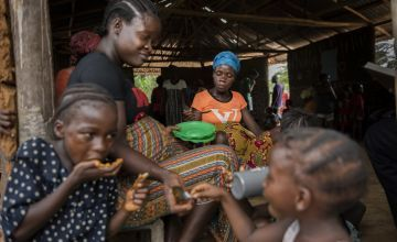 Marie Sawmada eats a meal with two of her children - Love and Baby, provided at the end of a nutrition training session at her local Mothers Group. Photo: Nora Lorek