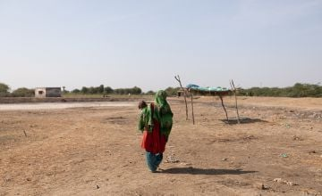 A woman carries her baby through the dusty landscape of Sindh province, Pakistan