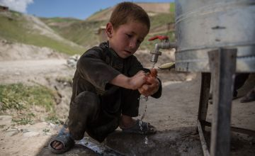 Child uses handwashing station in Afghanistan