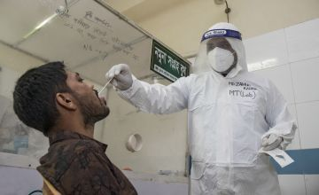 A man in PPE takes a sample collection from a patient in Bangladesh