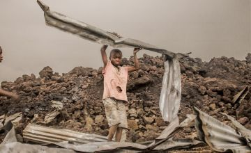 Amani (12) from the Buhene district in the north of Goma, collects the rubble after a volcanic eruption. Photo Esdras Tsongo Concern Worldwide