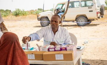 A Concern medical staff member distributes medication to a mother who has brought her child to be seen. The most common ailments are skin conditions, malaria and malnutrition. Photo: Gavin Douglas/Concern Worldwide