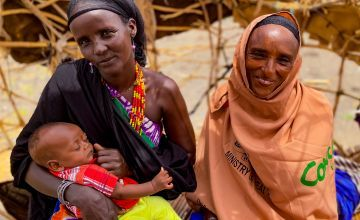 Two women smile at the camera as one of them breastfeeds her baby