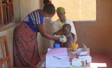 A community health worker checks a child for malnutrition using a MUAC band