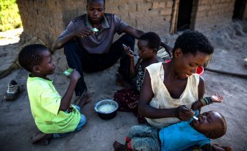 Eriq Kyugu, 28, and his wife Mado, 29, share breakfast with their children, 7 month old baby Bienheureux, 5 year old Bienaime and Esperance, a cousin in the village of Pension, Manono Territory