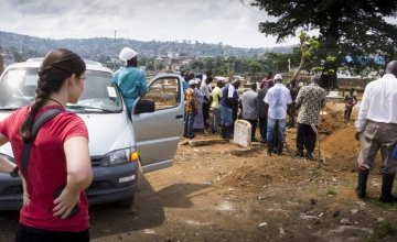 An observer from the Center for Disease Control (CDC) watches as a short graveside ceremony takes place at Kingtom cemetery in Freetown. Photo: Kieran McConville / Concern Worldwide.