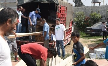 Concern employees organising the distribution of new tent kits (including wood, plastic sheeting etc) to families whose homes were recently burnt down. The tents are going to be built on this field in Northern Lebanon. Photograph by Mary Turner/Panos Pict
