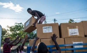 "Esparanza Maria, a 25-year-old day worker from Nhamatanda, helps load boxes containing essential household supplies from a warehouse to a truck. The items will be distributed the next day in the village of Ndeja. ""It makes me feel good to be able to help"