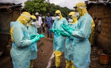 A burial team pray before they collect a corpse from inside a house in the east of Freetown Sierra Leone in 2015 Ebola outbreak. Photograph: Michael Duff