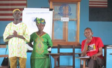 William Zoe, Martha Waaloe, community change makers and Harry Johnson, Concern staff member, at an engaging men and women in equality workshop, Liberia, 2013. Photo: Bernadette Crawford/ Concern Worldwide.