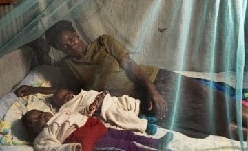 Florence Mutungi with six-month-old twin daughters Blessings and Precious. The family's Community Health Volunteer has encouraged them to use the mosquito net provided when the girls were born to protect them against malaria. Photo: Peter Caton