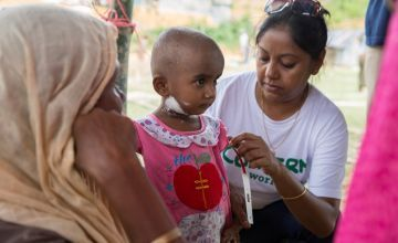 Concern's Asfia Azim measures the upper arm circumference of two year old Lukia* at the nutrition center at Moynadhona refugee camp for Rohingya in Cox's Bazar, Bangladesh.