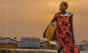 A woman walks to collect water early in the morning at a camp for IDPs in Bentiu, South Sudan, 2018. Photo: Welthungerhilfe/Stefanie Glinski.