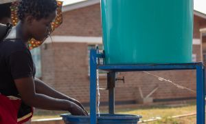 Jessy, washing hands at the hospital's entrance before seeing her patient. Photo: Henry Mhango