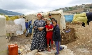 Arwa with her grandchildren in front of her makeshift shelter in an informal tented settlement near the Syrian border.
