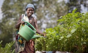 A woman stands in a vegetable garden holding a watering can