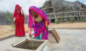 Two women take water out of a tank